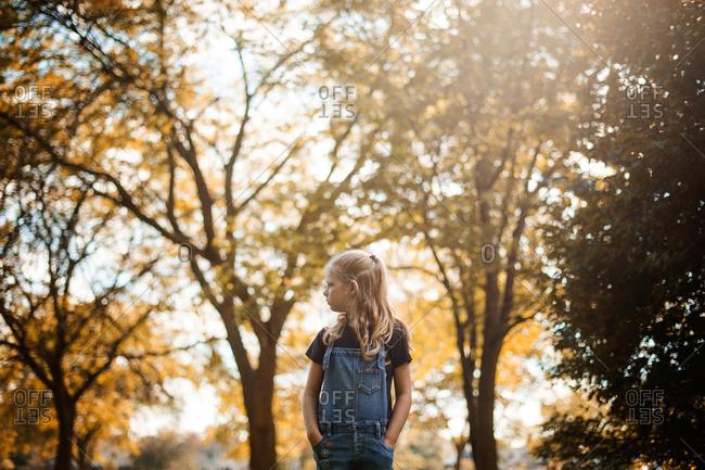 Girl walking by trees in fall