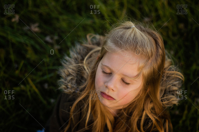 Blonde girl lying in the grass with her eyes closed