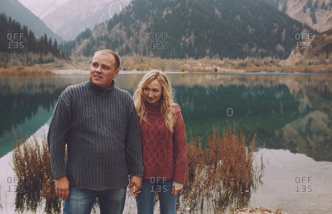 Couple standing at the mountain lake