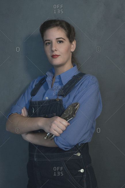 Retro 1940s female laborer in dungarees holding tool