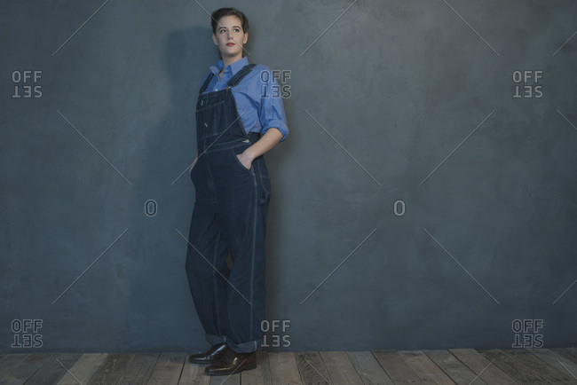 Retro 1940s woman in dungarees standing indoors leaning against grey wall