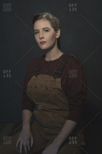 Retro 1940s brunette woman in dungarees against grey wall