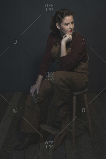 Vintage 1940s brunette female worker in dungarees holding tool