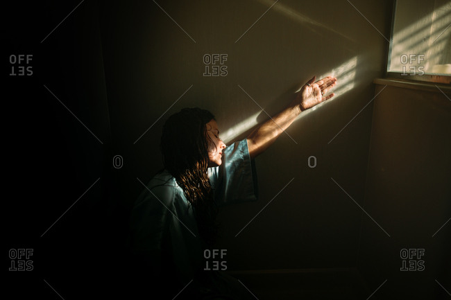 Woman with arm up against wall along stripes from window blinds shadows
