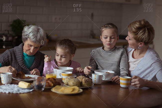 Multi-generation family having breakfast in kitchen at home