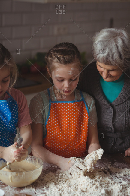 Grandmother and granddaughters preparing cupcake in kitchen at home