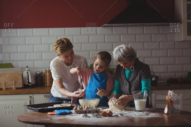 Multi-generation family preparing cupcake in kitchen at home