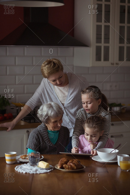 Multi-generation family using digital tablet in kitchen at home