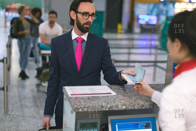 Airline check-in attendant handing passport to commuter at counter in airport terminal