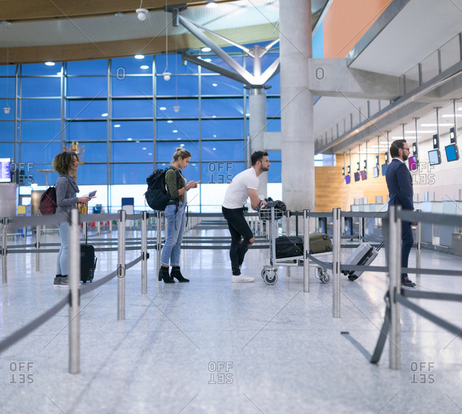 Commuters standing in queue for check-in at airport