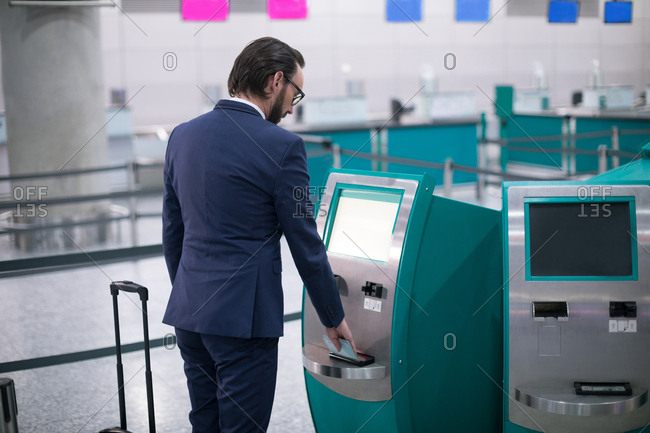 Businessman using airline ticket machine at airport