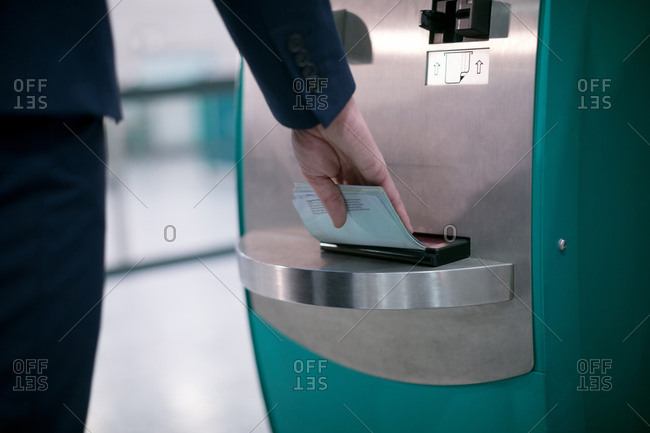 Mid section of businessman using airline ticket machine at airport