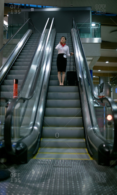 Woman standing on escalator with luggage at airport