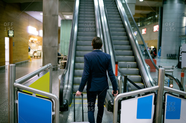 Businessman walking with luggage towards escalator at airport