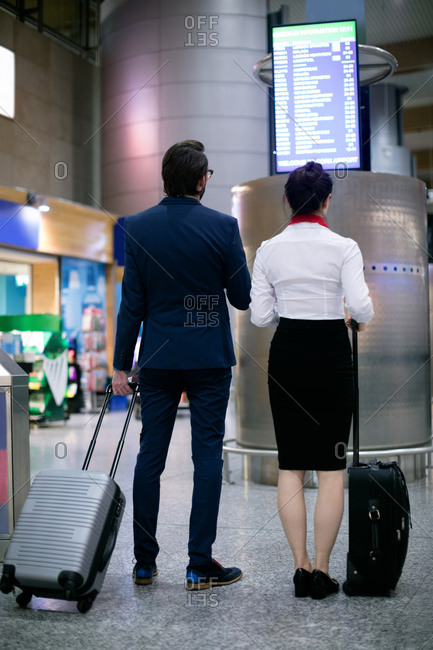 Businessman and woman looking at departure board in airport