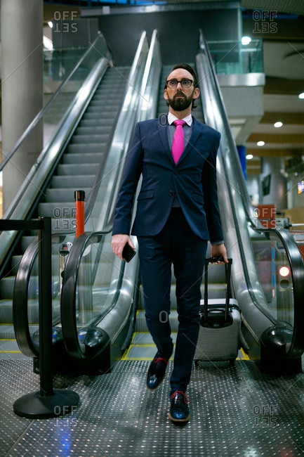 Businessman walking with luggage from escalator at airport