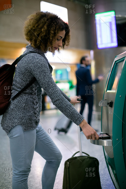 Woman using airline ticket machine at airport