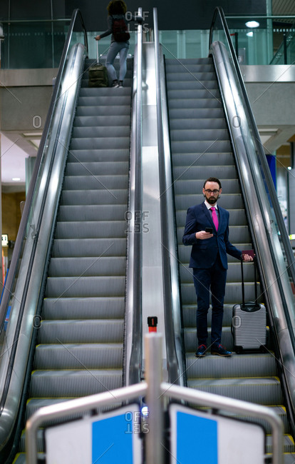 Businessman standing on escalator with luggage at airport