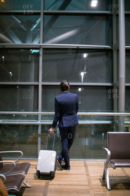 Rear view of businessman waiting at waiting area at airport