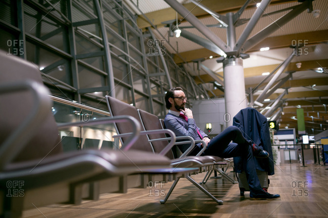 Thoughtful businessman waiting in waiting area at airport