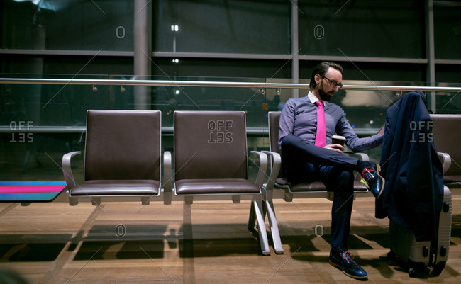 Businessman having coffee while waiting in waiting area at airport