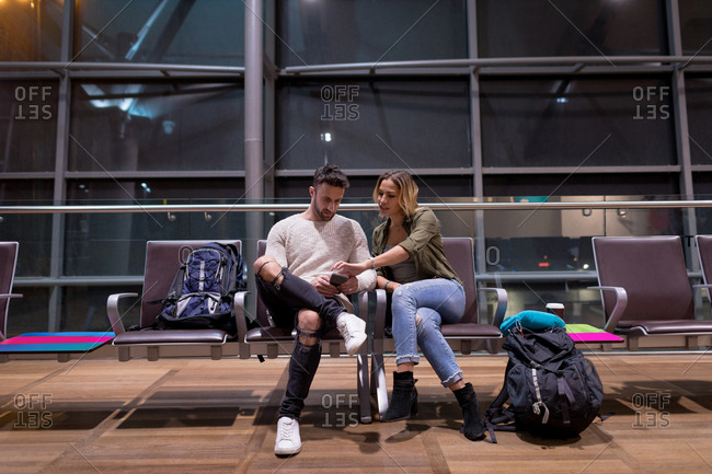 Couple using mobile phone in waiting area at airport