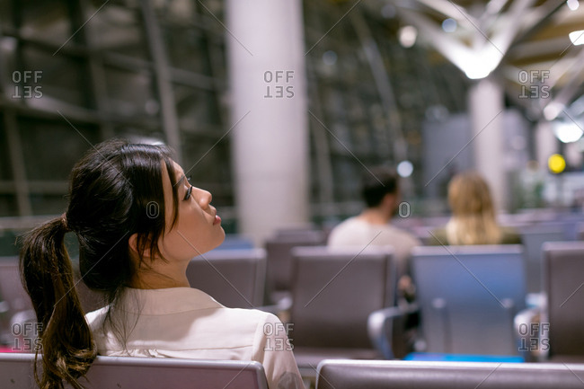 Thoughtful woman waiting in waiting area at airport