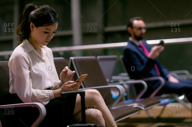 Woman using mobile phone in waiting area at airport