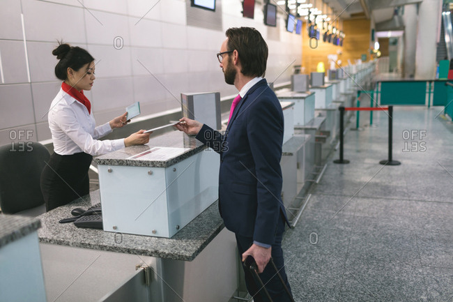 Airline check-in attendant handing digital tablet to commuter at counter in airport terminal