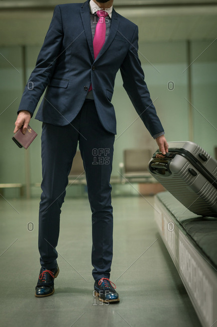 Businessman taking their baggage from baggage carousel at airport