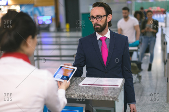 Airline check-in attendant checking ticket of commuter on digital tablet at airport