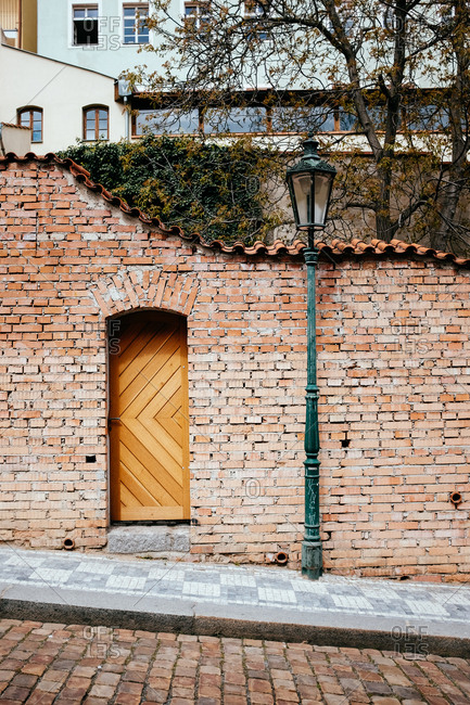 Brick building with wooden door and lamppost in Old Town Prague
