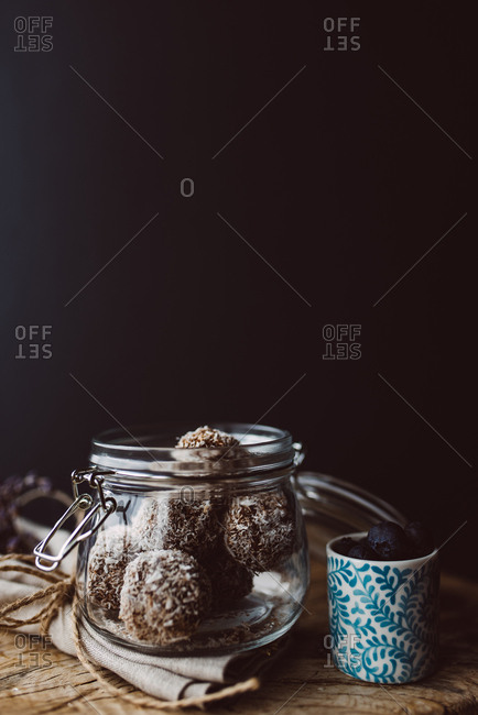 Raw coconut balls in a jar next to a cup of blueberries
