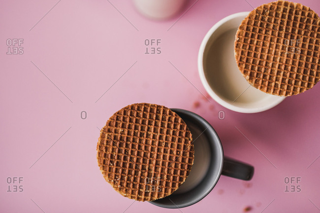 Aerial shot of two cups of milk covered with waffles on a pink background