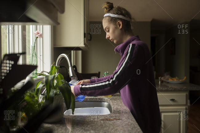 Young lady washing dishes at the sink