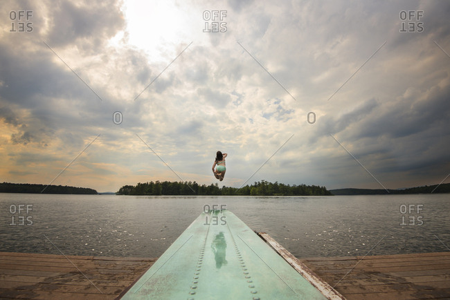 View straight down diving board of teen girl jumping into lake