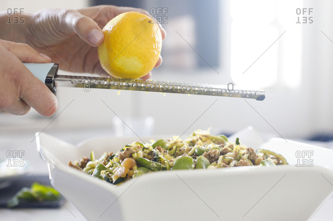 Recipe step grating lemon over fresh meal