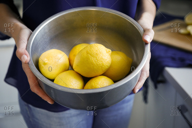 Close detail of hands holding pot of fresh lemons