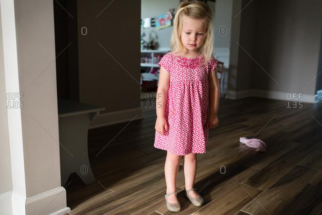 Sad little girl standing on hardwood floor