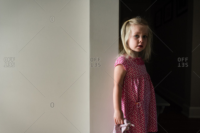 Small blonde girl leaning against wall frame