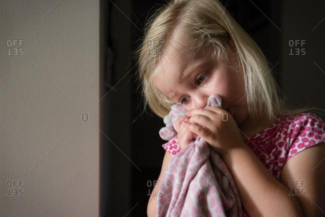 Sleepy little girl clutching soft toy blanket