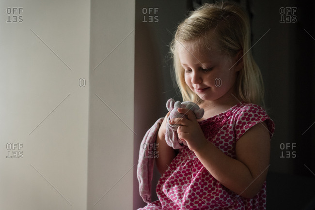 Happy toddler admiring stuffed toy