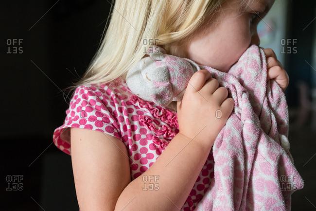 Side profile of blonde girl with giraffe blanket