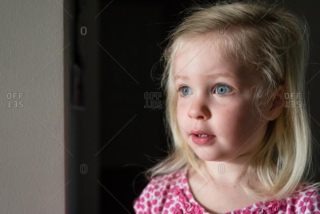 Wide eyed toddler looking off towards window sunlight