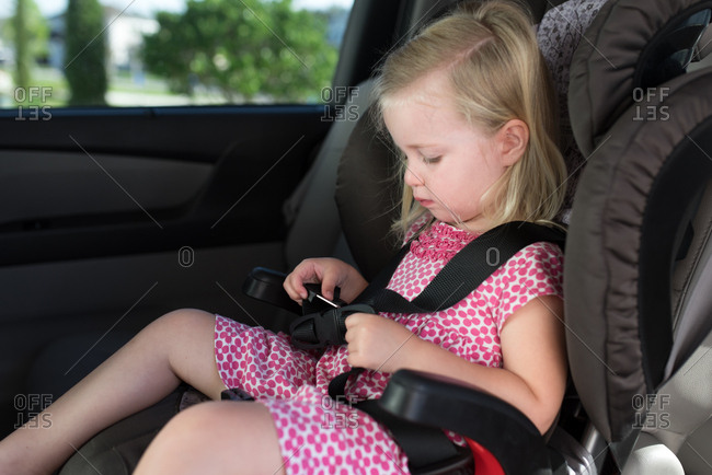 Little girl buckling herself up in car seat
