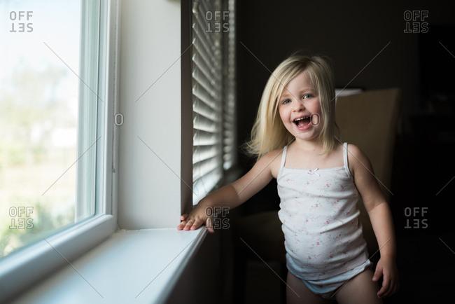 Portrait of joyful little girl laughing by window