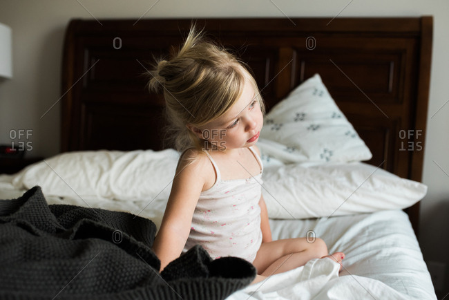 Little girl sitting on big bed looking a bit worried