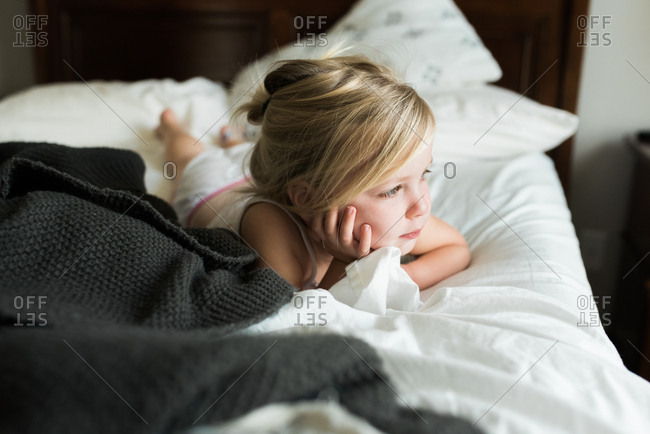 Little girl lying on big bed with chin in hand deep in thought