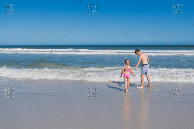 Dad offering hand to encourage daughter to go into the sea at the beach