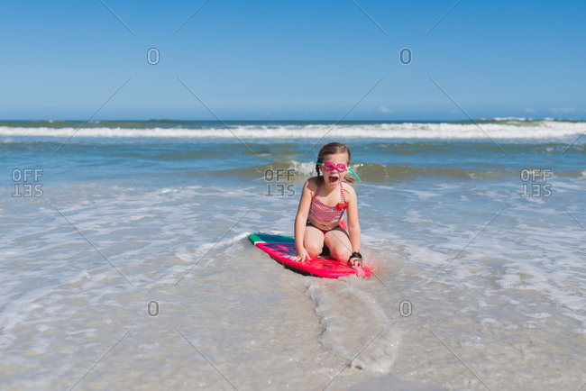 Little girl squealing with joy after riding a wave on a body board at beach